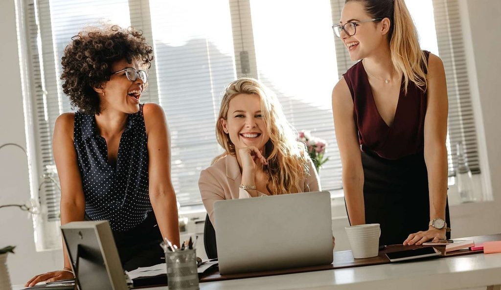 Group of three diverse women in office